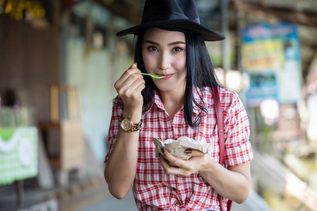 Giovani turisti asiatici della ragazza delle donne che mangiano godere del gelato del cocco
