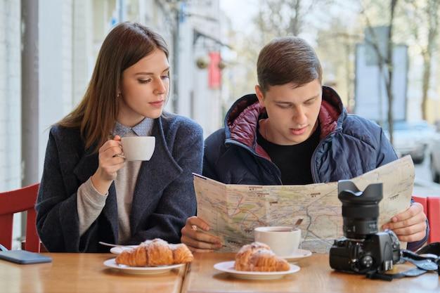 Giovani turisti che leggono la mappa della città in caffè all'aperto