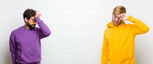 Giovani uomini alla moda che sembrano stressati, stanchi e frustrati, asciugano il sudore dalla fronte, si sentono senza speranza ed esausti contro il muro di piastrelle bianche