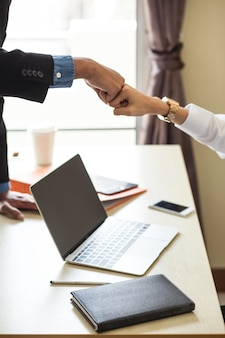 Giovani uomini d'affari salutano la segretaria con un pugno