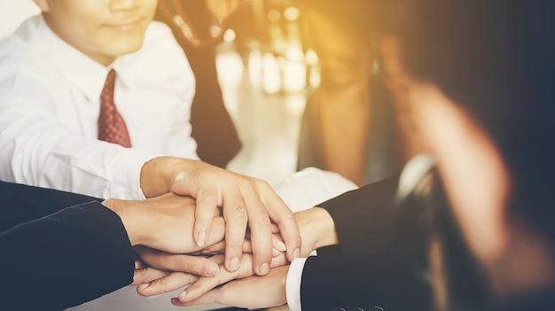 Giovani uomini d'affari si uniscono le mani per condurre gli affari insieme per l'unità come una squadra.