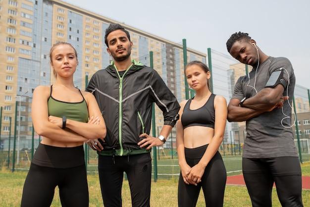 Giovani uomini e donne sportivi in activewear in piedi in ambiente urbano su stadio all'aperto con edifici