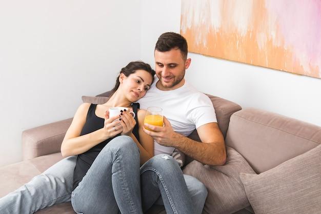 Giovani vetri sorridenti della tazza e del succo di caffè della tenuta delle coppie sul sofà
