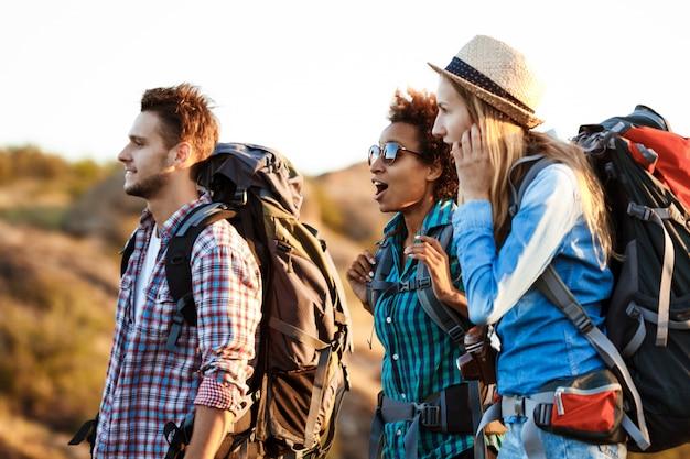 Giovani viaggiatori allegri con zaini sorpresi, sorridenti, che camminano nel canyon