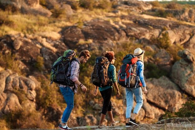 Giovani viaggiatori allegri con zaini sorridenti, camminando nel canyon