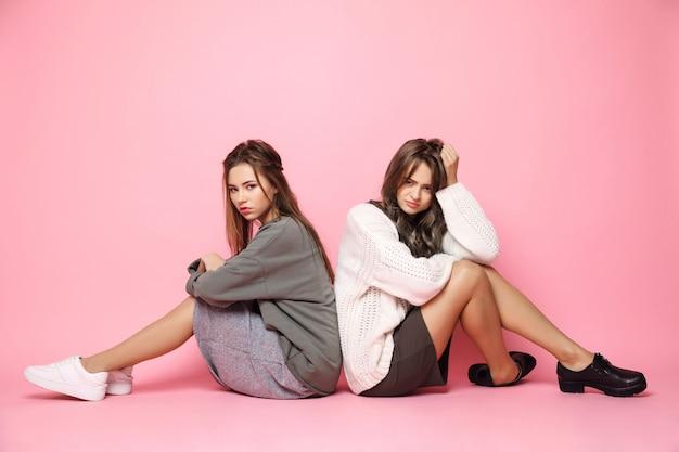 Giovani womans dispiaciuti che si siedono sul pavimento rosa