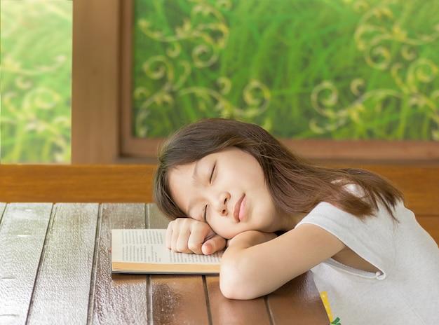 Gir asiatico che dorme mentre impara