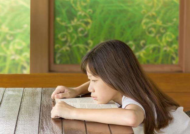 Gir asiatico stanco sullo scrittorio mentre imparando