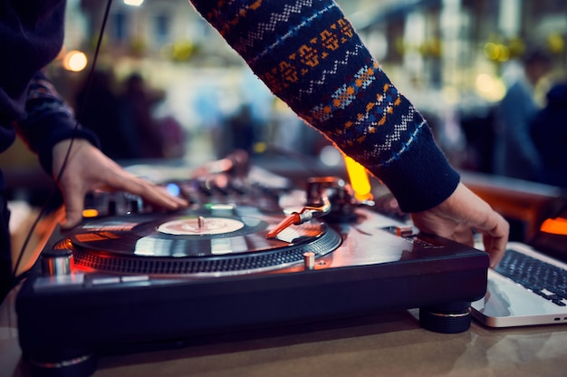 Giradischi, mano di dj sul disco in vinile al night club.