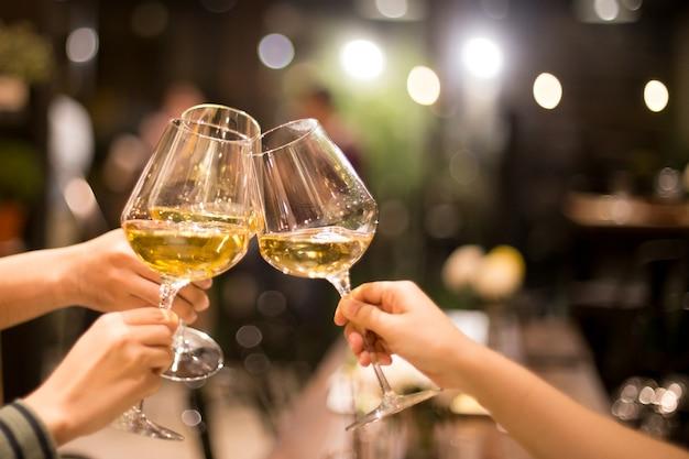 Girato in alto iso con gruppo di luce bassa di amici che brindano al vino