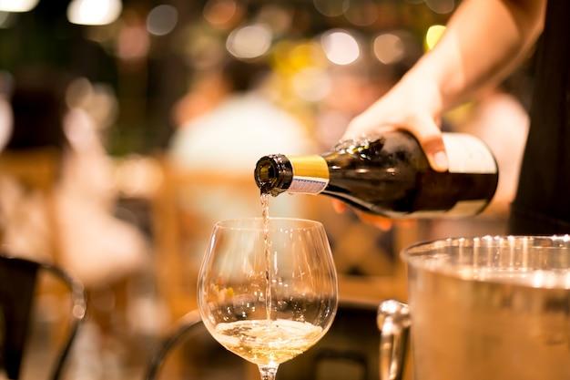 Girato in alto iso con poca luce, versando il vino dalla bottiglia in un bicchiere