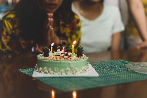 Girato in bassa luce donna che soffia sulle candele sulla torta di compleanno con gli amici.