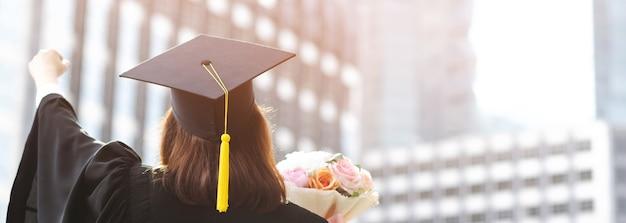 Girato lato posteriore giovane studentessa in mano alzando le braccia sul pugno pollice in alto e in possesso di un mazzo di fiori durante l'inizio successo laureato dell'università, congratulazioni educazione concetto.