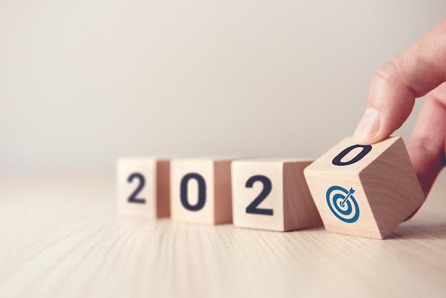 Giri la mano sopra i cubi di legno di legno con il nuovo anno 2020 e il concetto dell'icona di obiettivo.