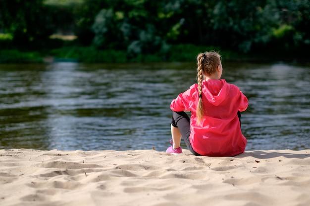 Girk magro bianco rosso con treccia, indossato in impermeabile rosa, seduto su una riva sabbiosa del fiume, vista da dietro.