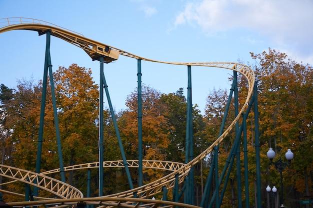 Giro fresco moderno delle montagne russe del primo piano contro il parco di divertimenti e cielo blu e nuvole bianche, festival di divertimento