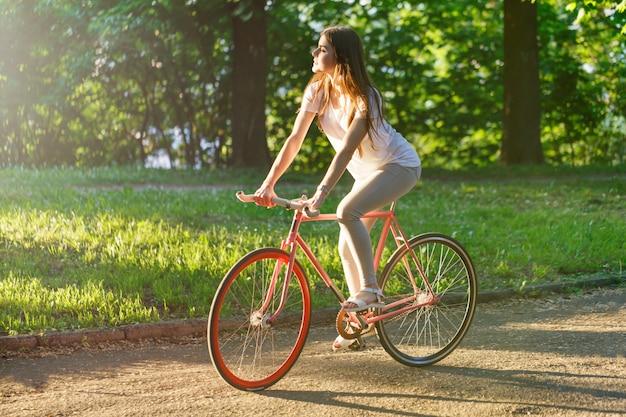 Giro grazioso della ragazza sulla bicicletta rosa