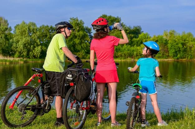 Giro in bici per famiglie all'aperto, genitori attivi e bambino in bicicletta e relax vicino al bellissimo fiume