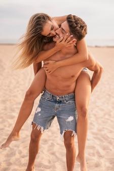 Giro sulle spalle con coppia in spiaggia