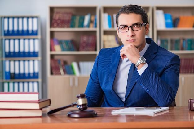 Giudice bello con il martelletto che si siede nell'aula di tribunale