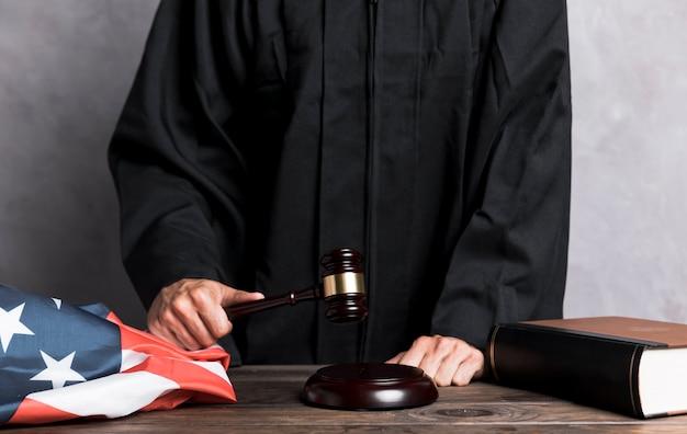 Giudice del primo piano che colpisce il martelletto
