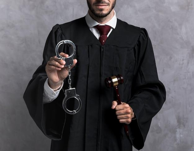 Giudice del primo piano con le manette e il martelletto