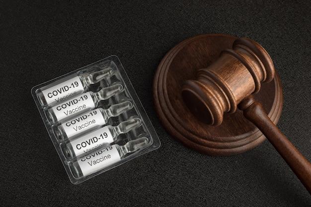 Giudice martelletto e fiale con lettere covide19. leggi contro il coronavirus covid-19