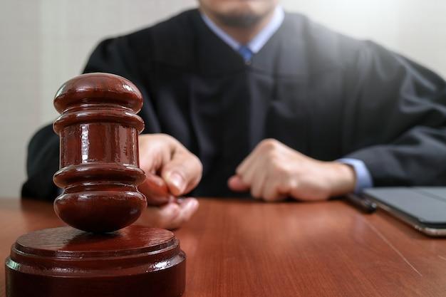Giudice maschio in un'aula di tribunale che colpisce il martelletto, funzionante con il computer digitale della compressa