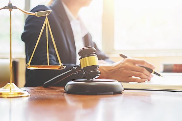 Giudichi il martelletto con gli avvocati della giustizia che hanno gruppo che si incontra al fondo dello studio legale.