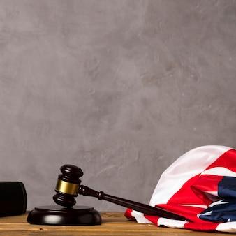 Giudichi il martelletto e la bandiera degli stati uniti con il fondo dello stucco