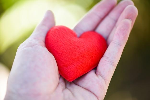 Give love man holding piccolo cuore rosso nelle mani per amore san valentino dona aiuto fai attenzione al calore dell'amore