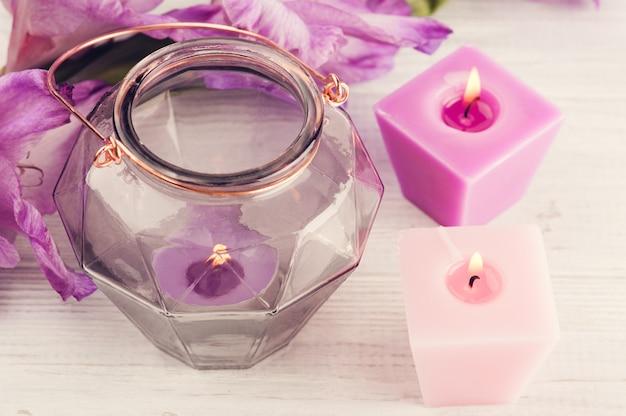 Gladiolo viola e candele accese sulla tabella bianca