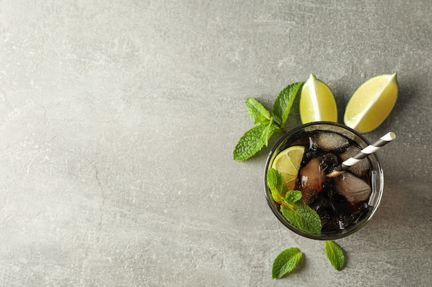 Glasse con cola fredda e agrumi sul tavolo grigio, vista dall'alto