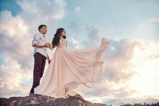 Gli abbracci delle coppie innamorate baciano la vita felice, l'uomo e la donna, il tramonto, i raggi del sole, una coppia innamorata che si guarda negli occhi
