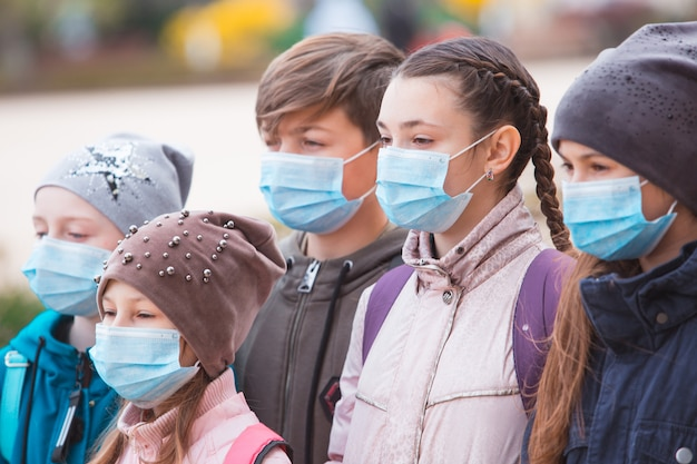 Gli abitanti della città adulti e bambini che indossano maschere osservano la quarantena