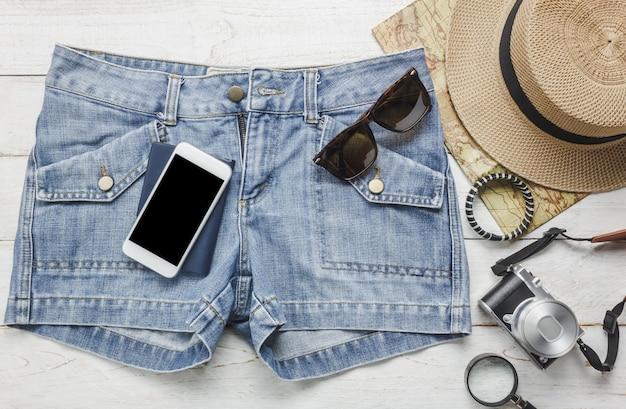Gli accessi di vista superiore per viaggiare con il concetto di abbigliamento femminile. telefono cellulare bianco, cappello, mappa, macchina fotografica, collana, pantaloni e occhiali da sole sul tavolo di legno bianco.