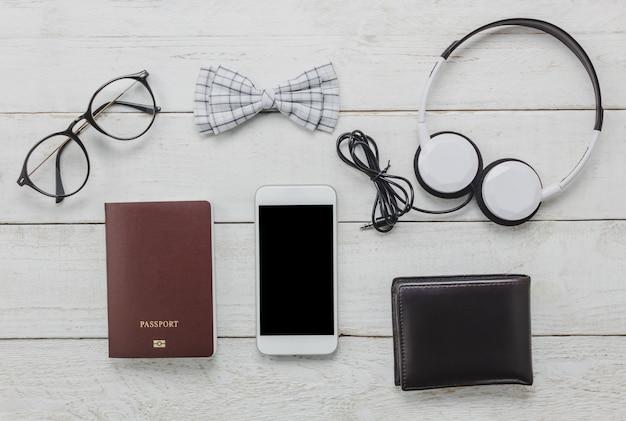 Gli accessi di vista superiore per viaggiare con il concetto di abbigliamento uomo. cravatta di arco, passaporto su sfondo in legno. occhiali da vista, cuffie, portafoglio, albero sul tavolo di legno.