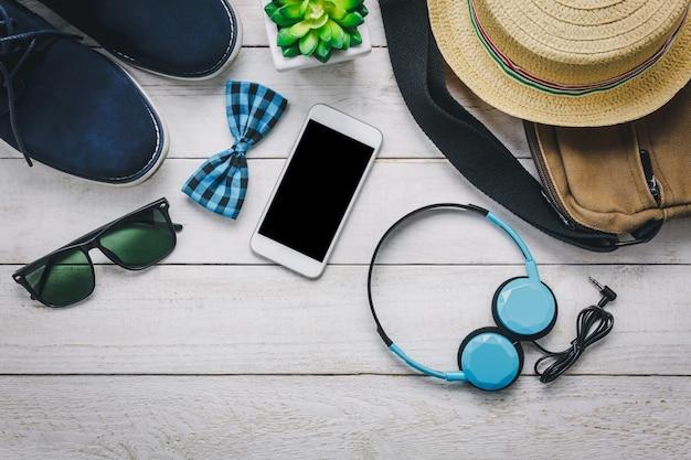 Gli accessi di vista superiore per viaggiare con il concetto di abbigliamento uomo. telefono cellulare e cuffie su legno background.bow cravatta, portafoglio, occhiali da sole, scarpe, borsa e cappello sul tavolo di legno.
