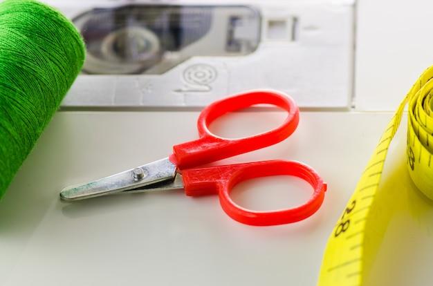 Gli accessori per il cucito si trovano su una macchina da cucire bianca