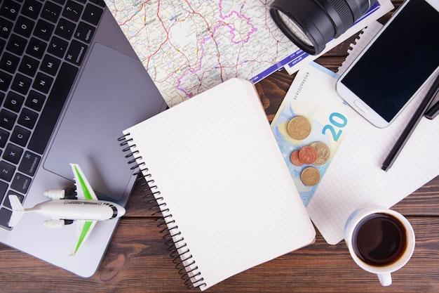 Gli accessori per scrittori di blogger di viaggio distesi distesi su legno scuro bianco.