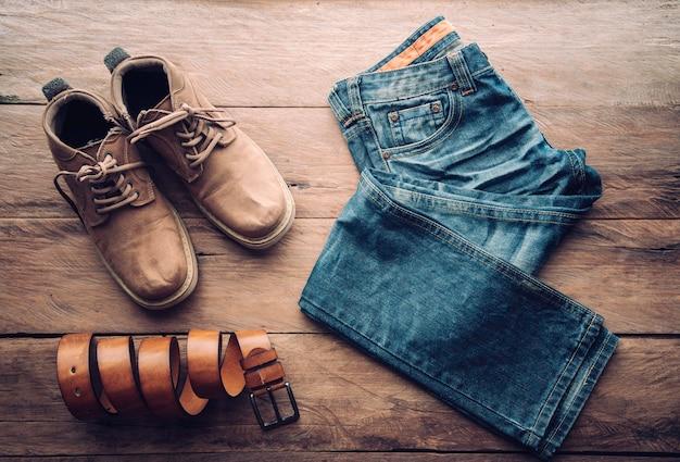 Gli accessori per uomo giacciono sul pavimento di legno