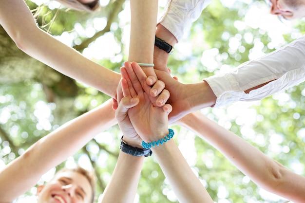 Gli adolescenti hanno unito le loro mani in un cerchio