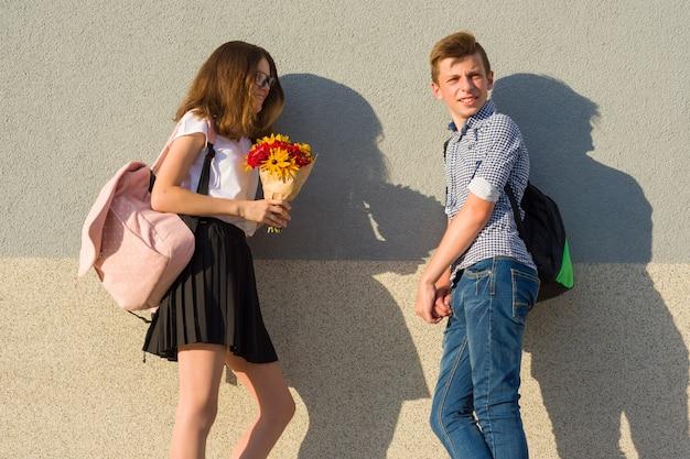 Gli adolescenti ragazzo e ragazza camminano, ridono, parlano