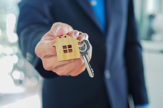 Gli agenti di vendita a domicilio stanno consegnando le chiavi di casa ai nuovi proprietari
