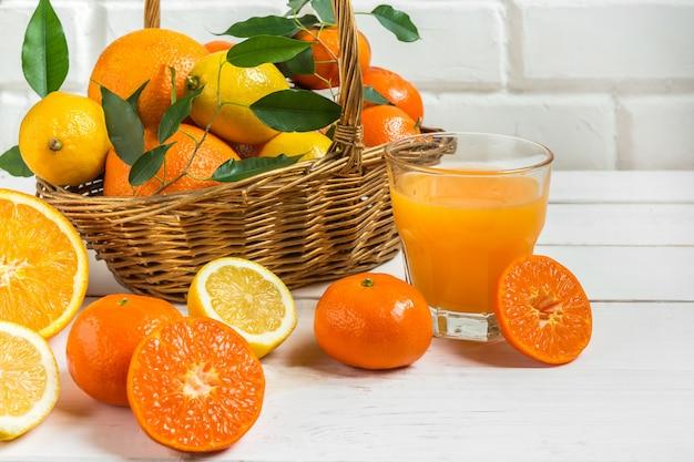 Gli agrumi del limone arancio in un canestro e un succo su un fondo leggero, alimentano l'alimento sano