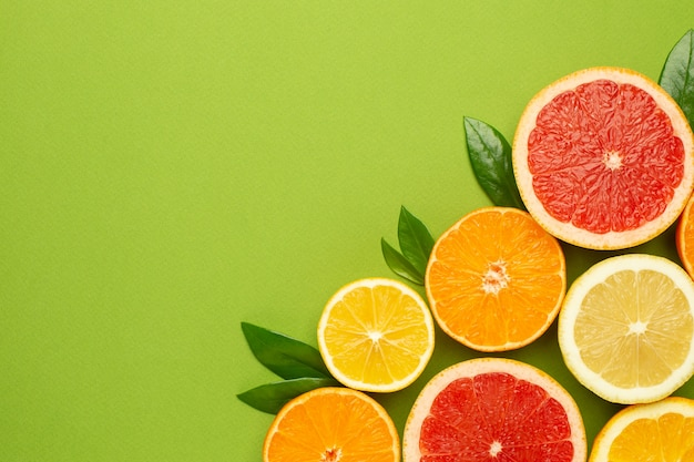 Gli agrumi fruttifica su sfondo verde con copyspace, frutta flatlay, composizione minima estiva con pompelmo, limone, mandarino e arancia