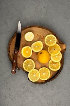 Gli agrumi hanno affettato una vista dall'alto fette di limone sulla scrivania in legno marrone e sul pavimento grigio