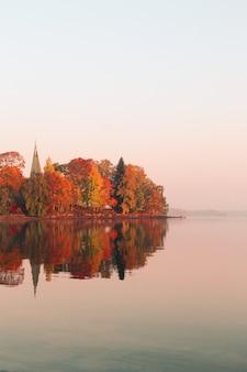 Gli alberi frondosi arancioni e verdi si avvicinano al lago