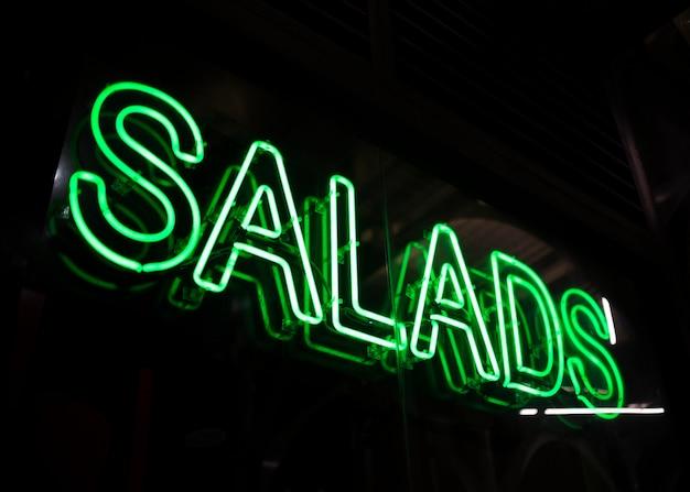 Gli alimenti a rapida preparazione delle insalate firmano dentro le luci al neon