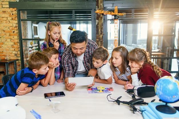 Gli allievi curiosi che guardano attentamente il loro insegnante maschio coreano usano il dispositivo del tablet per spiegare i principi di base elettronici a scuola.